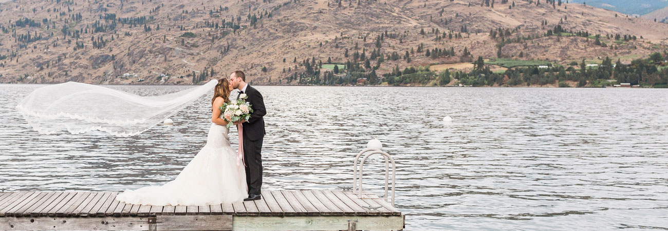 Newleds in wedding attire share a kiss standing upon a dock on the shore of Kelly's Resort